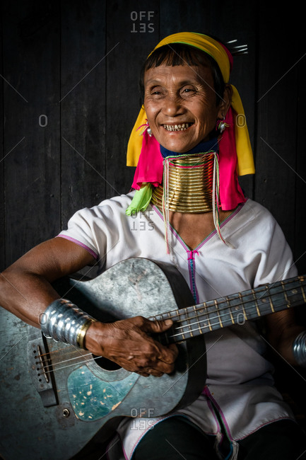 PADUANG PEOPLE,  HILL TRIBE, PAN PET VILLAGE, KAYAH STATE, MYANMAR - 24 January 2017: Portrait of local lady wearing brass coils placed around the neck, appearing to lengthen it, playing a guitar.