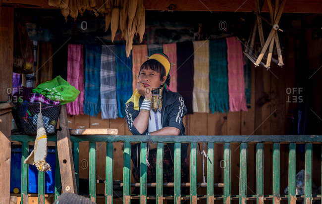 PADUANG PEOPLE,  HILL TRIBE, PAN PET VILLAGE, KAYAH STATE, MYANMAR - 28 January 2019: Portrait of local lady wearing brass coils placed around the neck, appearing to lengthen it, selling scarfs.