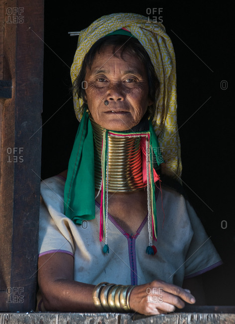 PADUANG PEOPLE,  HILL TRIBE, PAN PET VILLAGE, KAYAH STATE, MYANMAR - 24 November 2019: Portrait of local lady wearing brass coils placed around the neck, appearing to lengthen it, sat in window.