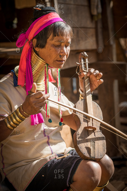 PADUANG PEOPLE,  HILL TRIBE, PAN PET VILLAGE, KAYAH STATE, MYANMAR - 20 January 2020: Portrait of local lady wearing brass coils placed around the neck, appearing to lengthen it, playing violin.