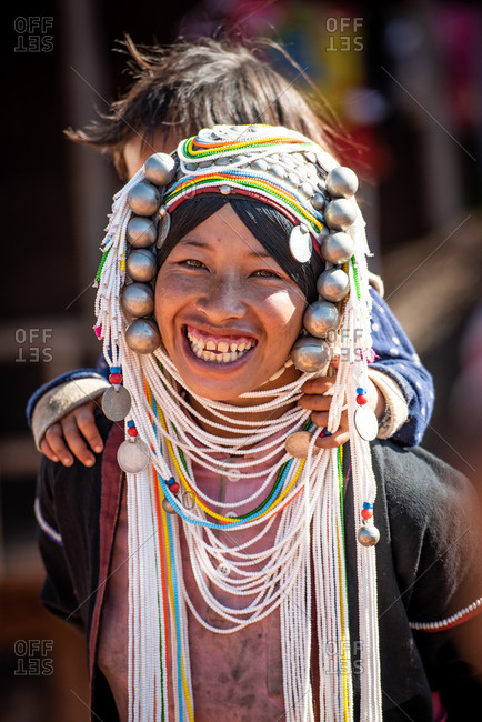 AKHA HILL TRIBE, HOKYIN VILLAGE, MYANMAR - 18 January 2017: Close up portrait of young hill tribe women in traditional dress and decorated head dress carrying a small child.