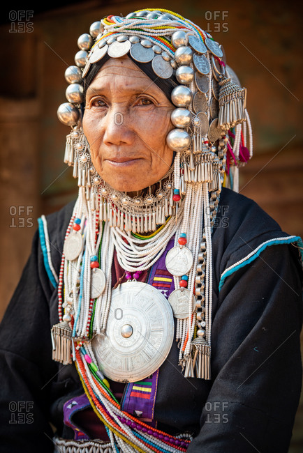 AKHA HILL TRIBE, HOKYIN VILLAGE, MYANMAR - 18 January 2017: Close up portrait of elderly hill tribe women in traditional dress,  decorated head dress and large pendant.