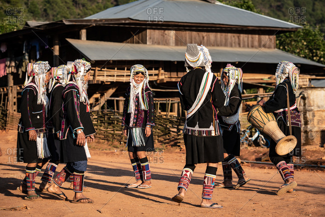 AKHA HILL TRIBE, HOKYIN VILLAGE, MYANMAR - 22 January 2019: Women in traditional dress play the drum whilst dancing as part of a musical performance in their village.