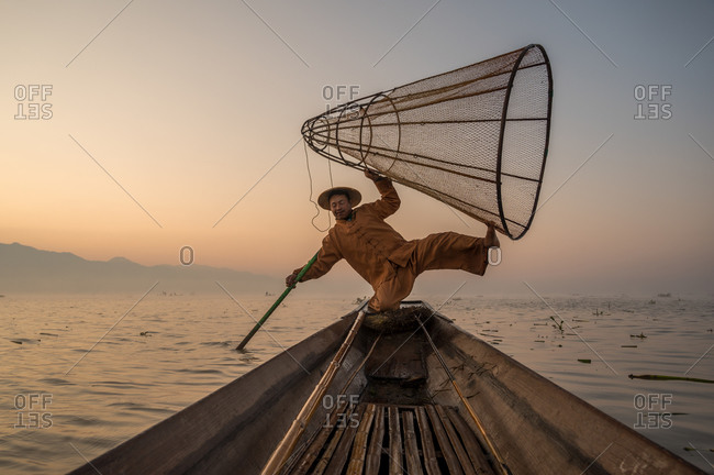 INTHA FISHERMEN, INLE LAKE, SHAN STATE, MYANMAR - 18 January 2020: Traditional fishing technique using a conical net at sunrise, shot low angle from inside boat.