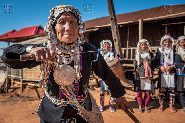 AKHA HILL TRIBE, HOKYIN VILLAGE, MYANMAR - 18 January 2017: Women in traditional dress dances with her knife in village square as part of musical performance.
