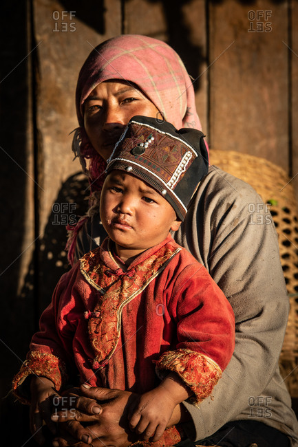 AKHA HILL TRIBE, HOKYIN VILLAGE, MYANMAR - 22 January 2019: Close up portrait of hill tribe mother and child in traditional dress and decorated head dress.