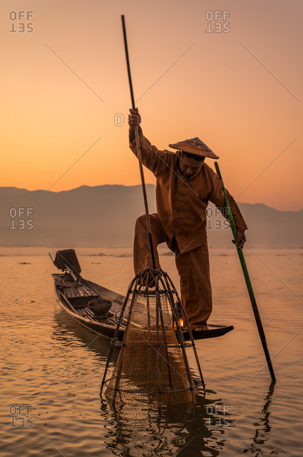 INTHA FISHERMEN, INLE LAKE, SHAN STATE, MYANMAR - 18 January 2020: Traditional fishing technique using a trident spear, lamp and a conical net at sunrise.