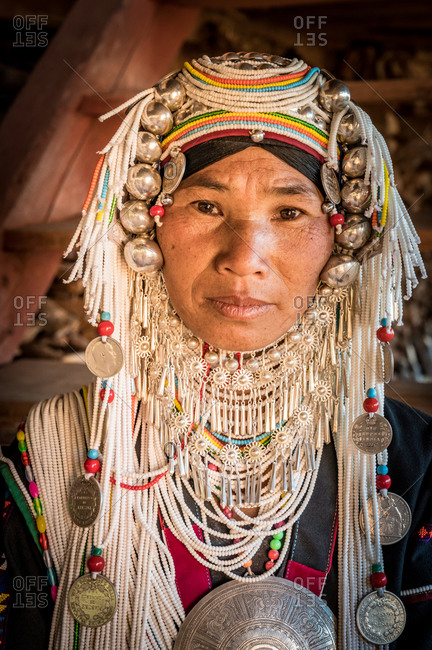 AKHA HILL TRIBE, HOKYIN VILLAGE, MYANMAR - 15 January 2020: Close up portrait of elderly hill tribe women in traditional dress and decorated head dress.