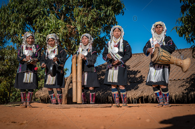 AKHA HILL TRIBE, HOKYIN VILLAGE, MYANMAR - 15 January 2020: Women in traditional dress playing musical instruments, singing and dancing in their village.