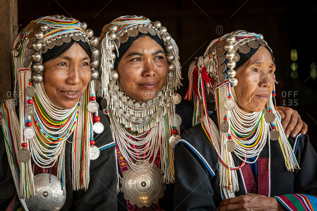 AKHA HILL TRIBE, HOKYIN VILLAGE, MYANMAR - 22 January 2019: Close up portrait of three hill tribe women in traditional dress and decorated head dress.