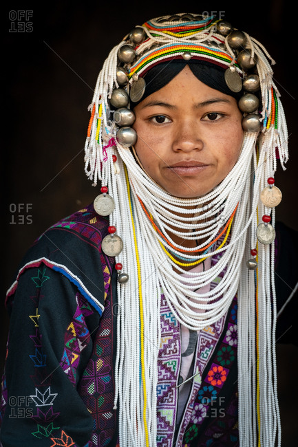 AKHA HILL TRIBE, HOKYIN VILLAGE, MYANMAR - 22 January 2019: Close up portrait of young hill tribe women in traditional dress and decorated head dress.
