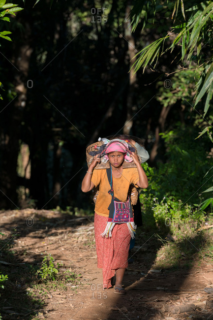 AKHA HILL TRIBE, HOKYIN VILLAGE, MYANMAR - 22 January 2019: Hilltribe ladies trek back to village through forest after long day working in the field.