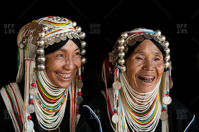 AKHA HILL TRIBE, HOKYIN VILLAGE, MYANMAR - 22 January 2019: Close up portrait of two hill tribe women in traditional dress and decorated head dress.