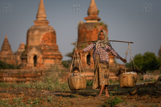 BOY IN BASKET, TEMPLES OF BAGAN, MYANMAR - 31 January 2018: Farmer lady carries her son in basket while working with iconic temples in background.