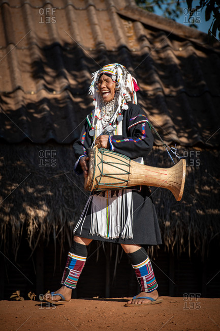 AKHA HILL TRIBE, HOKYIN VILLAGE, MYANMAR - 15 January 2020: Woman in traditional dress playing large drum whilst singing and dancing in her village.