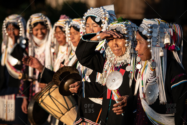 AKHA HILL TRIBE, HOKYIN VILLAGE, MYANMAR - 22 January 2019: Women in traditional dress playing musical instruments and clapping while line dancing.