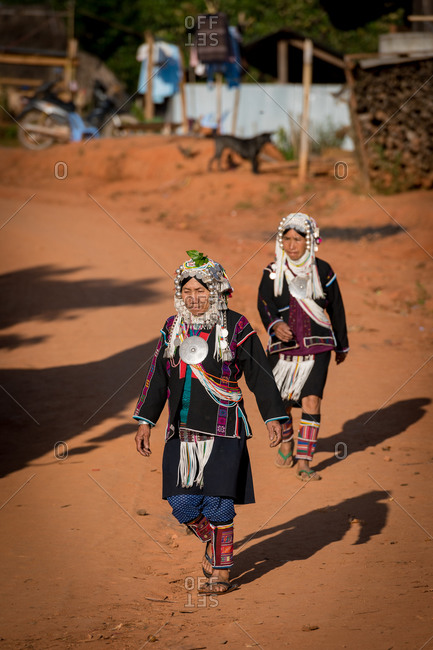 AKHA HILL TRIBE, HOKYIN VILLAGE, MYANMAR - 22 January 2019: Hilltribe ladies in traditional costume walk through village streets in warm light.