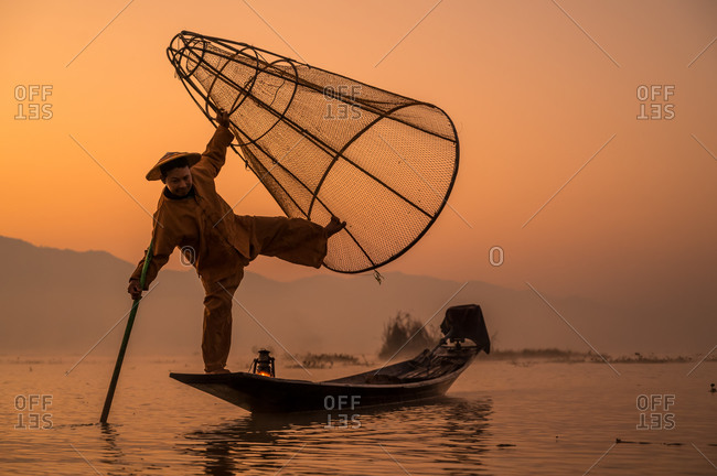 INTHA FISHERMEN, INLE LAKE, SHAN STATE, MYANMAR - 18 January 2020: Traditional fishing technique using a lamp and a conical net at sunrise.