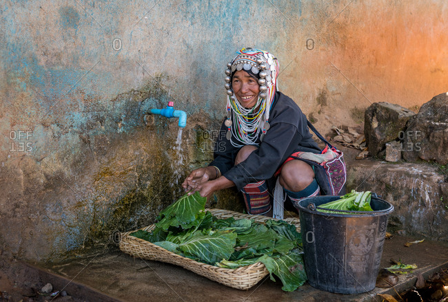 AKHA HILL TRIBE, HOKYIN VILLAGE, MYANMAR - 24 January 2018: Woman in traditional costume washing cabbage leaves at communal water supply.