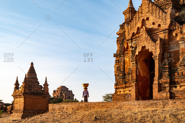 SUNSET, TEMPLES OF BAGAN, MYANMAR - 22 January 2020: Lone burmese lady carries basket on her head through the historic temples of Bagan.