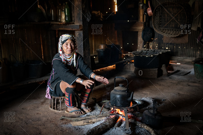 AKHA HILL TRIBE, HOKYIN VILLAGE, MYANMAR - 24 January 2018: Woman in traditional costume boils tea on firewood typical local kitchen.