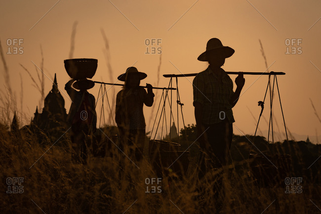 SUNSET, TEMPLES OF BAGAN, MYANMAR - 31 January 2018: Silhouette of workers carrying baskets and iconic Bagan temple shape at sunset.