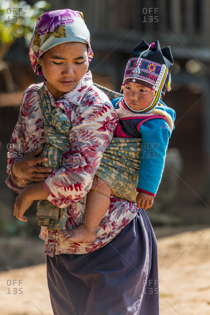 AKHA HILL TRIBE, HOKYIN VILLAGE, MYANMAR - 22 January 2019: Hill tribe lady ties baby in traditional wrap sling on mothers back.