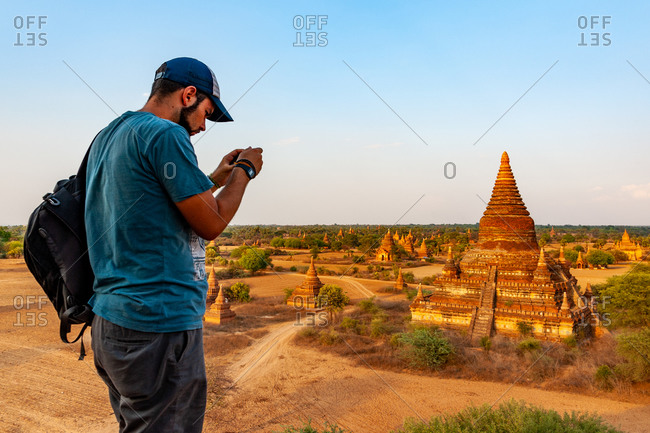 EVENING, TEMPLES OF BAGAN, MYANMAR - 23 April 2013: Photographer checks shot from vantage point across numerous heritage temples.