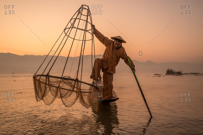 INTHA FISHERMEN, INLE LAKE, SHAN STATE, MYANMAR - 18 January 2020: Traditional fishing technique using a conical net at sunrise.