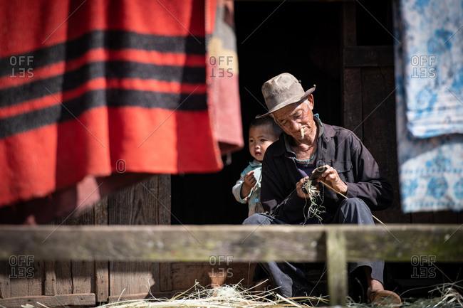 AKHA HILL TRIBE, HOKYIN VILLAGE, MYANMAR - 22 January 2019: Grandpa shaves down bamboo on his doorstep with grandson.