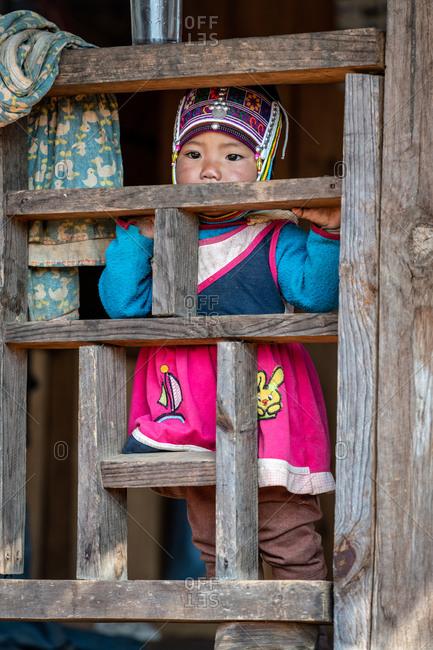 AKHA HILL TRIBE, HOKYIN VILLAGE, MYANMAR - 22 January 2019: Young hilltribe infant is kept safe on wooden balcony.
