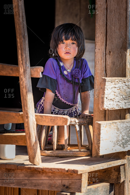 AKHA HILL TRIBE, HOKYIN VILLAGE, MYANMAR - 15 January 2020: Young ethnic minority girl looks out from her balcony.