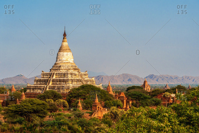 Shwesandaw Pagoda in evening light with numerous small temples in foreground.