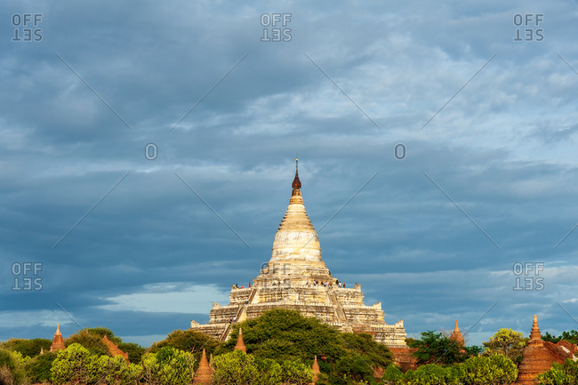 Shwesandaw Pagoda in evening light against clouds.