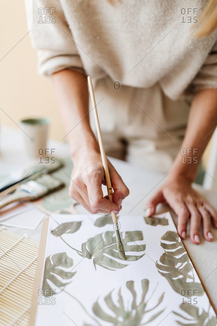 Unrecognizable crop female artist standing at table and painting green leaves of monstera plant on sheet of paper in art workshop