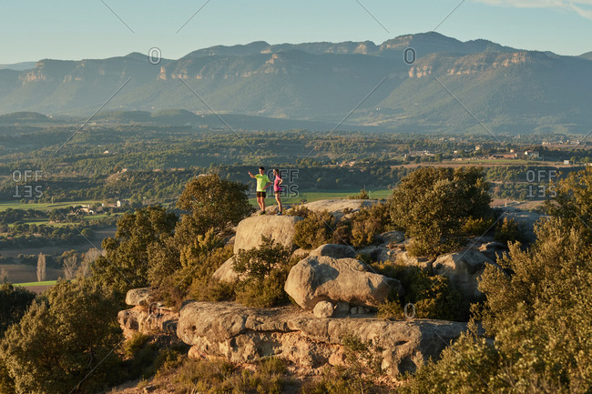 Remote view of sportsman and sportswoman standing on hill and having break during training in mountains at sunset