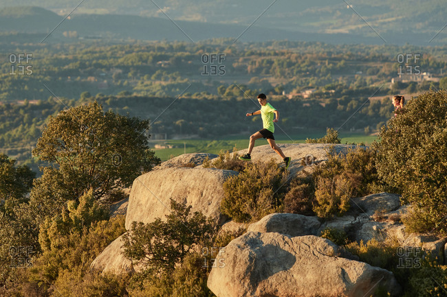 Side view of slim male runner jumping on rocks in mountains at sunset in evening during active training