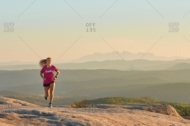 Enduring female athlete running up rocky hill at sunset in mountains during active cardio training