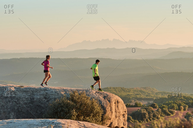 Sportsman and sportswoman running on slope in highland terrain during cardio training at sundown in summer