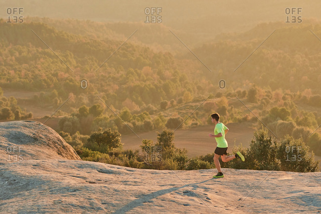 Side view of slim male runner running on rocks in mountains at sunset in evening during active training