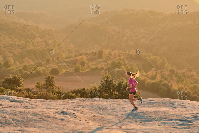 Side view of enduring female athlete running up rocky hill at sunset in mountains during active cardio training