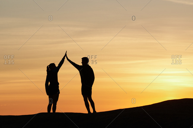 Side view of friendly sportsman and sportswoman giving high five to each other while standing on hill in highlands at sunset
