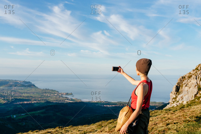 Side view of female adventurer standing on hill in highlands and taking photo of valley and sea at sunset during travel