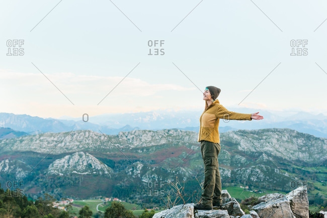 Side view of explorer standing on rough rock and enjoying scenery of highlands during vacation