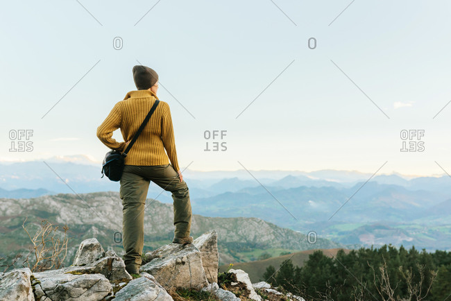 Back view of unrecognizable explorer standing on rough rock and enjoying scenery of highlands during vacation