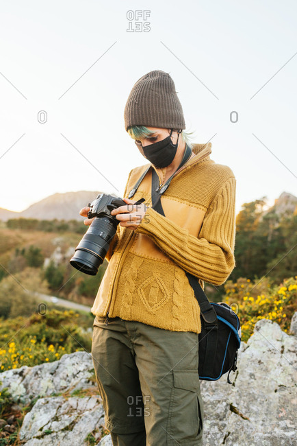 Traveling photographer in mask standing on rock and taking picture of landscape on professional photo camera during summer vacation in mountains