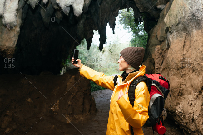 Side view of female explorer in outerwear standing near stone arch and taking selfie on smartphone near Cobijero Beach in Asturias