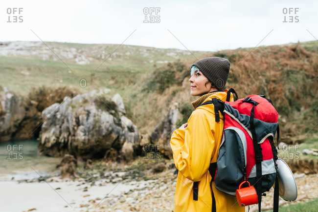 Side view of female explorer with backpack relaxing on stony coast of Cobijero Beach and admiring amazing view of lake on overcast day in autumn