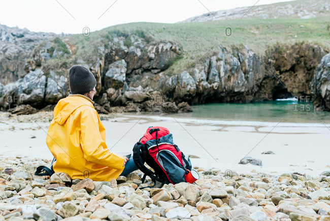 Back view of unrecognizable explorer with backpack relaxing on stony coast of Cobijero Beach and admiring amazing view of lake on overcast day in autumn