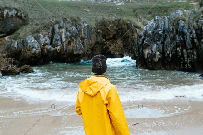 Back view of unrecognizable female explorer in yellow raining coat relaxing on stony coast of Cobijero Beach and admiring amazing view of lake on overcast day in autumn